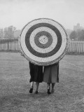 Two Women Holding Up Archery Target in Field