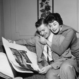 Wife Hugging Husband As He Sits in Armchair  Reading Newspaper