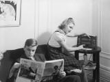 Boy and Girl (12-15) at Home Reading and Listening To Radio