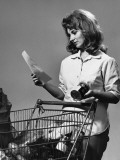Woman Reading Shopping List Beside Grocery Cart