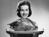 Woman Holding Platter With Roast Turkey