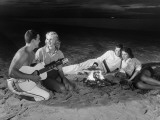 Two Couples on Beach Sitting Around Campfire