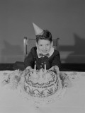 Boy Sitting at Table With Birthday Cake  Portrait