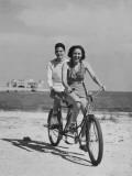 Teenage Boy and Girl Riding Bike Along Beach