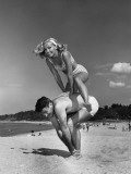 Couple Playing Leapfrog on Beach