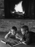 Two Boys Lying on Floor in Front of Fireplace  Reading Book