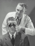 Optometrist Giving Man Eye Examination
