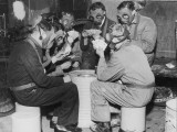 Group of Men Playing Cards  Wearing Gas Masks