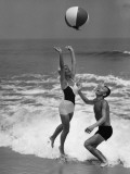 Young Couple Playing With Beach Ball at Water&#39;s Edge