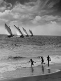 Three Boys Running Along Beach  Following Four Sailboats Out on Ocean