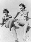 Two Young Women Wearing Swimsuits  Lying on Sand  Elevated View