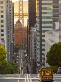 Cable Car Crossing California Street With Bay Bridge Backdrop in San Francisco  California  USA