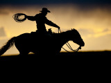 A Silhouetted Cowboy Riding Alone a Ridge at Sunset in Shell  Wyoming  USA