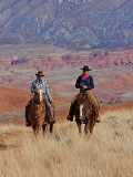 Cowboy and Cowgirl Riding Through Scenic Hills of the Big Horn Mountains, Shell, Wyoming, USA Papier Photo par Joe Restuccia III
