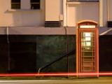 Night Shot of Uk Phonebox with Light Trails from Passing Car