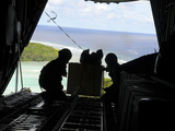 Airmen Push Out a Pallet of Donated Goods from a C-130 Hercules