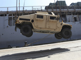 A Crane Lifts an M998 Humvee on the Flight Deck of USS Carter Hall