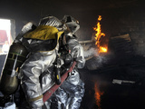Firefighters Extinguish a Fire in a Training Room During Live Burn Training