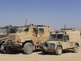 A British Armed Forces Snatch Land Rover Parked Next to Other Military Vehicles