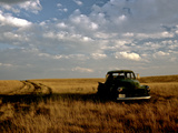 A Landscape of an Old Farm Truck in a Field at Sunset