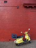 A Yellow Motor Scooter Against a Red Wall in Little Five Points