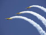 Three Yellow Planes Leave Arcs of White Smoke Behind