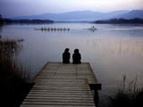 A Crew Boat and Women Sitting on a Dock on Lake Banyoles
