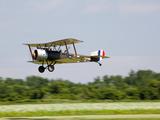 A Sopwith 1-1/2 Strutter Flies Low over a Grass Runway