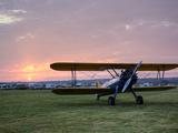 A Stearman Biplane on a Grass Airfield at Dawn