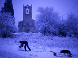 A Man Rolls a Ball of Snow Near the Church in Porqueres