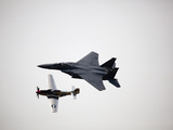 Two Military Planes from Different Eras Fly on a Gray Day