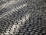 Patterns of Sunlight and Shadow on a Cobbled Road