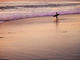 A Surfer Heads into the Waves Just as the Sun Is Setting