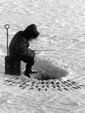 A Fisherman Fishes Through the Ice on Lake Huron