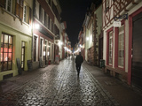 A Man Walks Down a Cobbled Street at Night