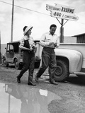 A Man and Woman Dodge a Puddle in the Street