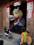 A Dragon Emerges from a Dragon Maker&#39;s Shop to Scare Children