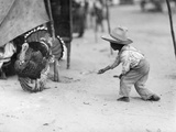 A Young Guatemalan Boy in a Straw Hat Tries to Coax a Turkey to Him