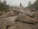 A Girl Hiking across Large Boulders in Early Morning Fog