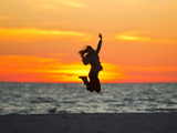 Silhouette of a Woman Jumping in Front of a Colorful Beach Sunset