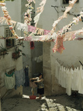Woman Hangs Laundry in Alley Below Billowing St Anthony Streamers