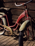 A Very Old Red Girls' Bike Rests on an Old Wooden Porch