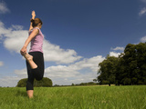 Young Woman Practicing Yoga in a Field