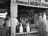 A Man Stands at the Edge of a Bar Surrounded by Bottles