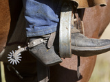 A Cowboy Boot and Spur in a Stirrup of a Saddle