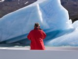 A Tourist in a Red Jacket on a Tour Boat Photographs an Iceberg