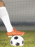 View of a football players foot on a soccer ball