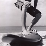 Young Man Standing on Surfboard on the Beach