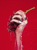 Woman's Hand Squeezing Red Grapes