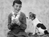 1920s 1930s Boy Eating Sandwich As Dog Stares At Food